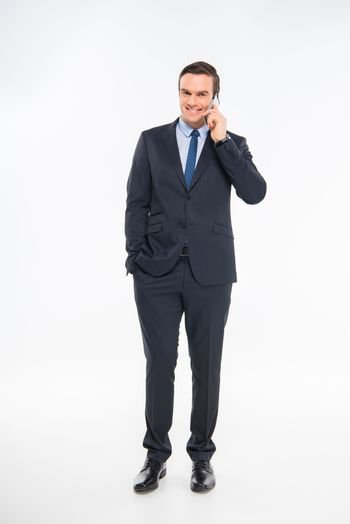 Professional young businessman talking on smartphone and smiling at camera