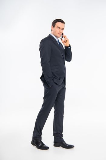 Serious young businessman talking on smartphone