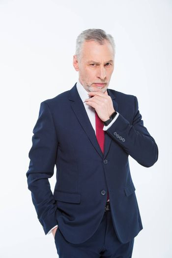 Handsome mature businessman with hand on chin looking at camera