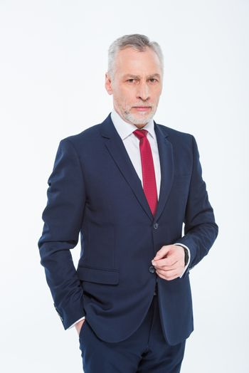 Handsome mature businessman with hand in pocket looking at camera
