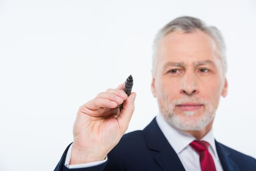 Handsome mature businessman writing with black marker