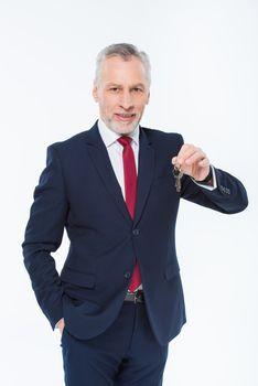 Smiling mature businessman holding keys and looking at camera