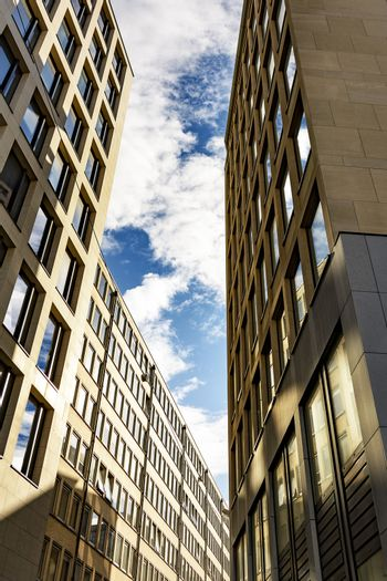 Skyscraper with square windows and sky with clouds.