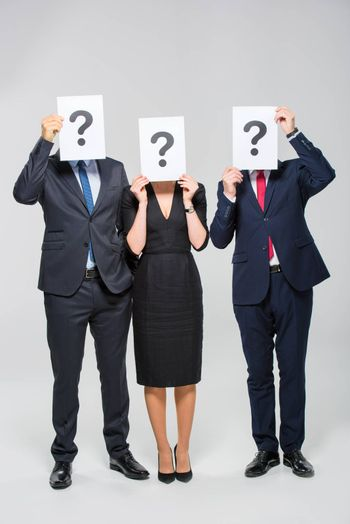 Three businesspeople holding cards with question marks