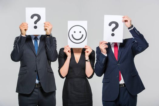 Three businesspeople holding cards with question marks and smiley on white