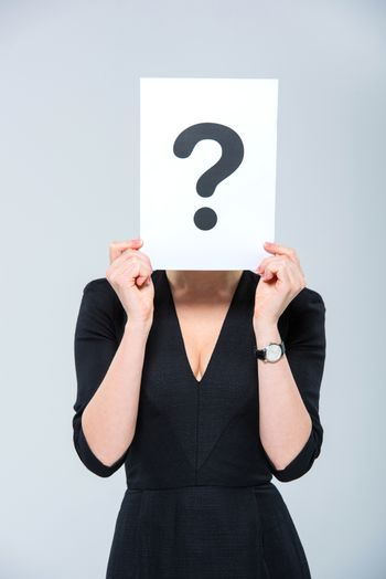 Young woman holding card with question mark and hiding her face behind it on white