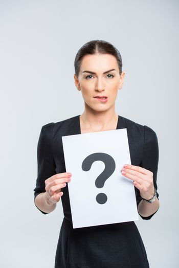 Young woman holding card with question mark and looking at camera on white