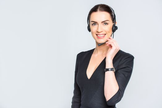 Young businesswoman in headset smiling and looking at camera on white