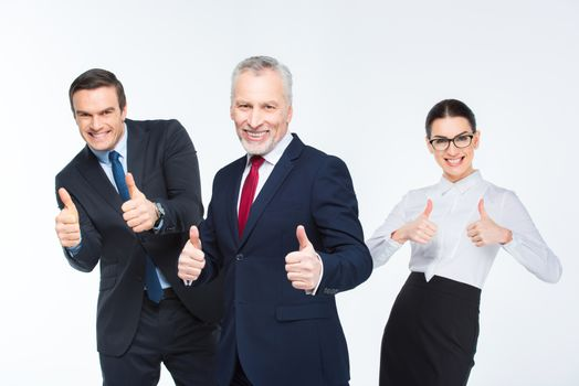 Three happy business people showing thumbs up on white