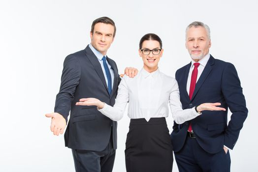 Three happy business people looking at camera and smiling on white