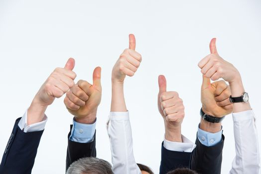 Partial view of hands of businesspeople showing thumbs up on white