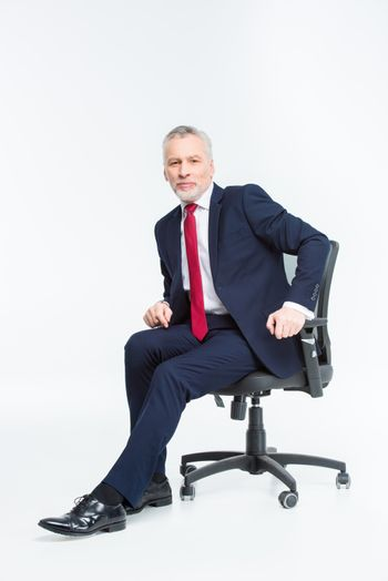 Mature businessman in office chair looking at camera on white