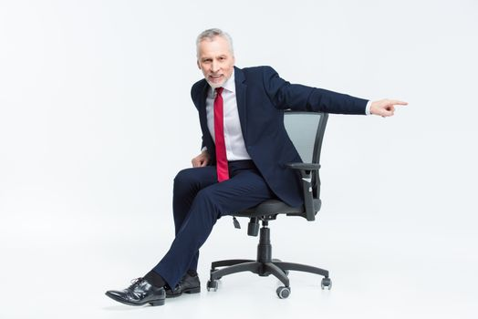 Smiling mature businessman in office chair pointing with his finger on white