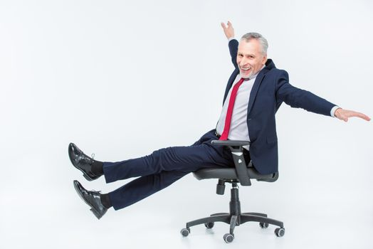 Excited mature businessman in office chair on white