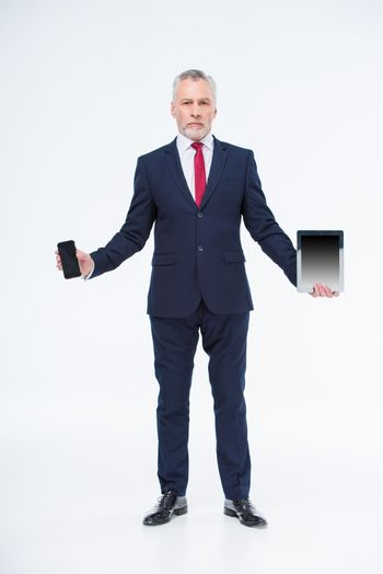 Mature businessman holding tablet computer and smartphone on white
