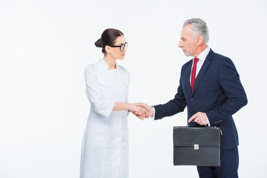 Two businesspeople shaking hands looking at each other on white