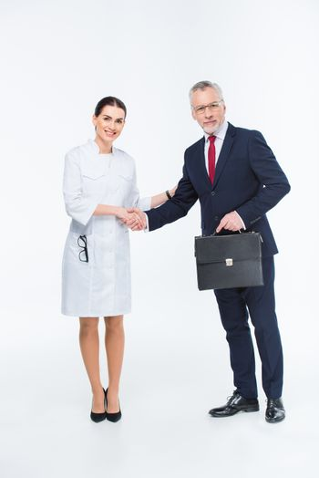 Two businesspeople shaking hands looking at camera on white