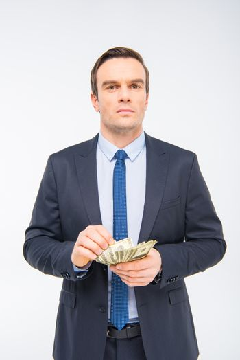 Young businessman holding dollar banknotes on white