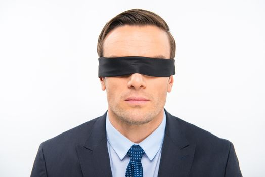 Portrait of young businessman in blindfold on white