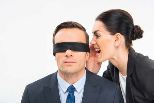 Young businesswoman screaming in the ear of businessman in blindfold on white