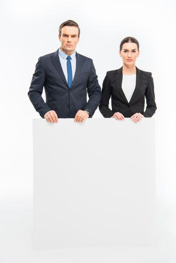 Businesspeople holding blank card and looking at the camera on white