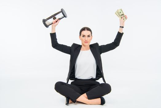 Young businesswoman sitting on floor and holding hourglass and money on white