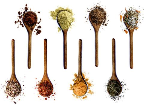 Collection of Various Spices in Wooden Spoons: Dried Paprika, Cumin Powder, Salt with Petals, with Chili and with Cayenne Pepper, Curry Powder and Thyme isolated on White background
