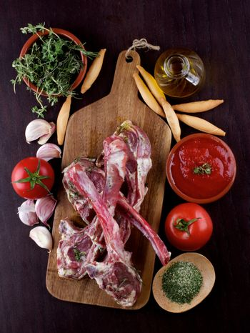 Raw Lamb Ribs with Tomatoes, Spices, Herbs, Olive Oil and Garlic on Wooden Cutting Board closeup on Dark Wooden background. Concept Ready to Roast