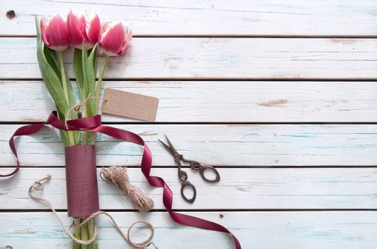 Tulips on a wooden background wtih gift tag