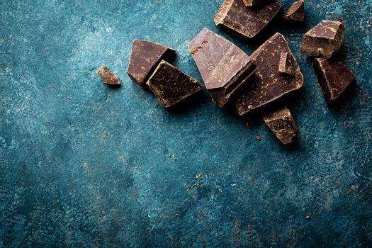 Dark chocolate pieces crushed on a dark background, view from above