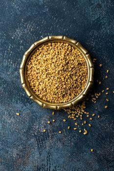 Fenugreek seeds on metal plate, spice, culinary ingredient