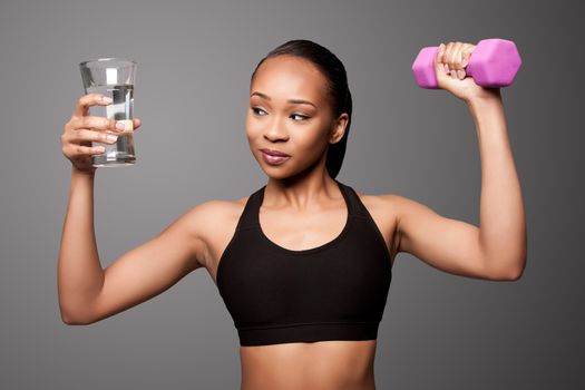 Beautiful healthy black asian woman with glass of water and dumbbell weight workout.