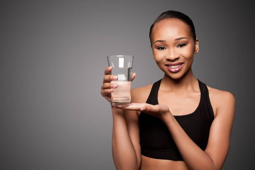 Beautiful happy smiling healthy black asian woman with glass of water, skincare concept.