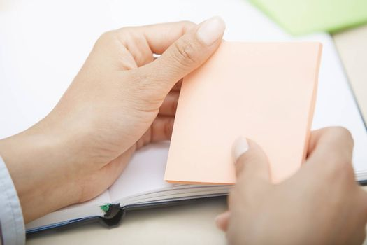 Hands holding pink sticky note with empty space