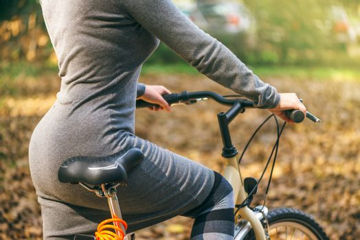 Sexy woman poses with her bicycle in park during autumn