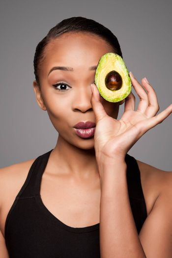 Beautiful healthy happy black asian woman holding delicious avocado super fruit in front of eye.