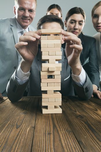 Business people team building wood puzzle tower