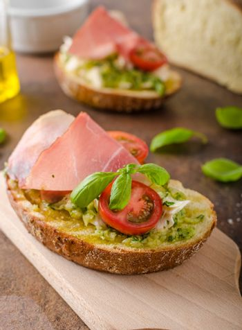 Toasted Tuscan bread with pesto and black forest ham, delicious homemade bread and pesto, topped with parmesan
