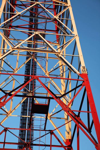 Red and white communication tower on blue sky
