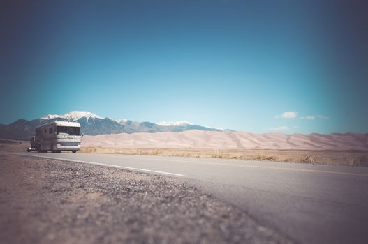 Recreation Vehicle with a Tow on the Colorado Road near Great Sand Dunes. Traveling in Class A RV Motorhome in America.