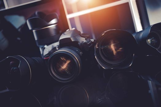 Pro Photography Technology. Professional Digital Photography Studio Equipment. Digital DSLR Camera and Few Prime Lenses on Glassy Desk.