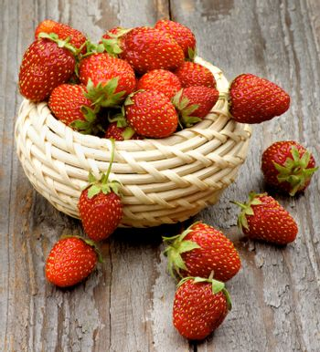 Arrangement of Fresh Ripe Forest Strawberries in Wicker Bowl closeup on Rustic Wooden background