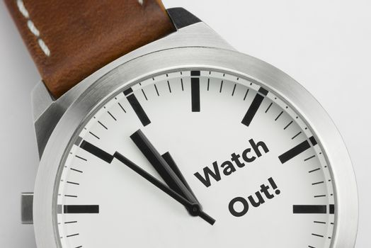 Analog watch with conceptual visualization of the text Watch Out