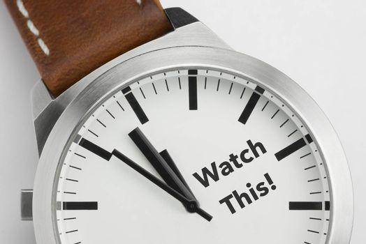 Analog watch with conceptual visualization of the text Watch This