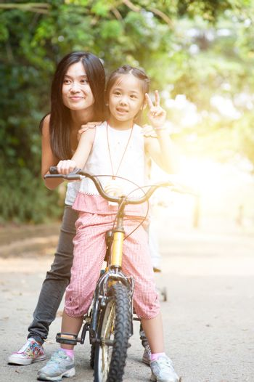 Parent and child biking outdoor.
