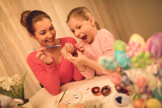 Beautiful happiness mother and daughter painting Easter egg at home.