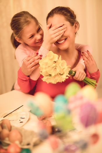 Cute little girl surprise her mother with bouquet yellow daffodils. Selective focus.