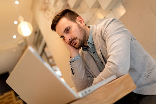 Young pensive businessman on a break in a cafe. He is working at laptop.