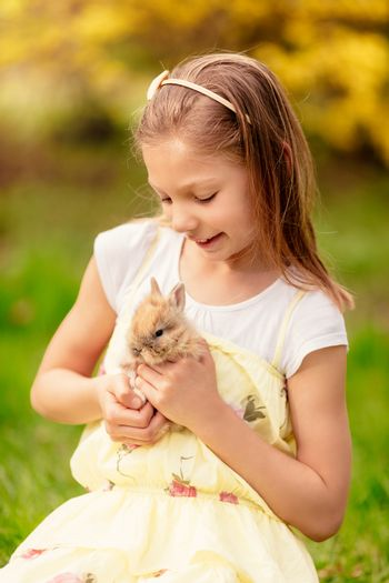 Beautiful smiling little girl holding cute bunny on nature in spring holidays.