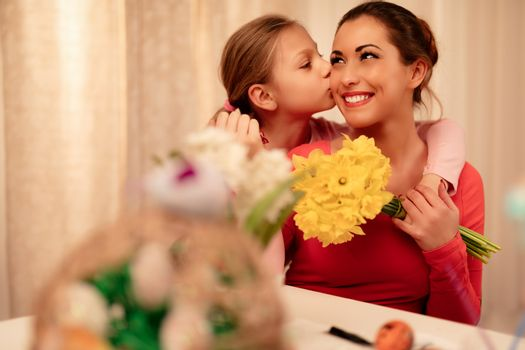 Cute little girl giving her mother bouquet yellow daffodils and kissing you.